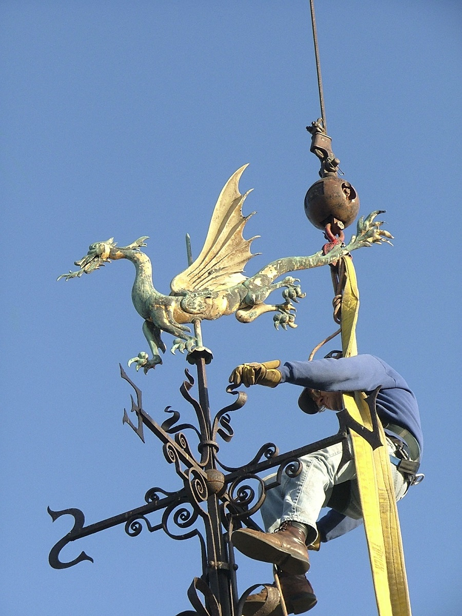 Man suspended from crane holds onto an elaborate metal weathervane in the shape of a dragon with decorative elements underneath