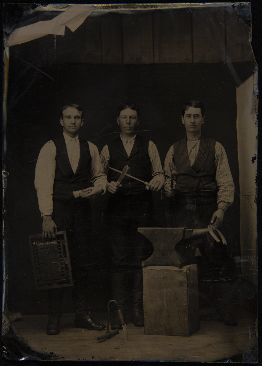Three men in vests and shirtsleeves standing behind an anvil on a wooden block, holding tools