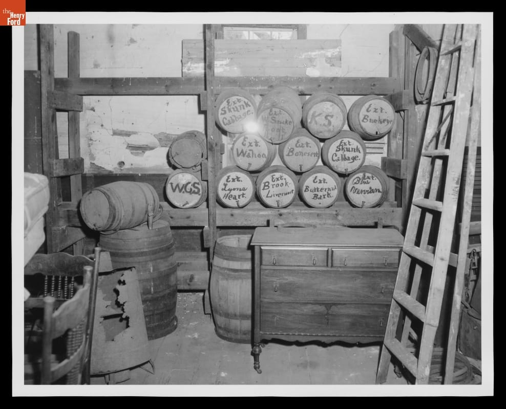 Dusty room containing furniture and a number of casks or barrels on their sides with handwriting on the tops