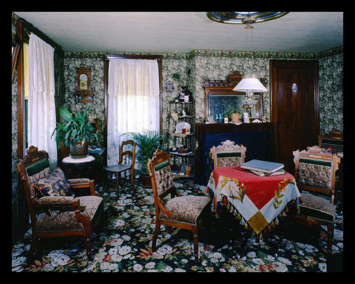 Room crowded with furniture and with busy floral carpeting and wallpaper