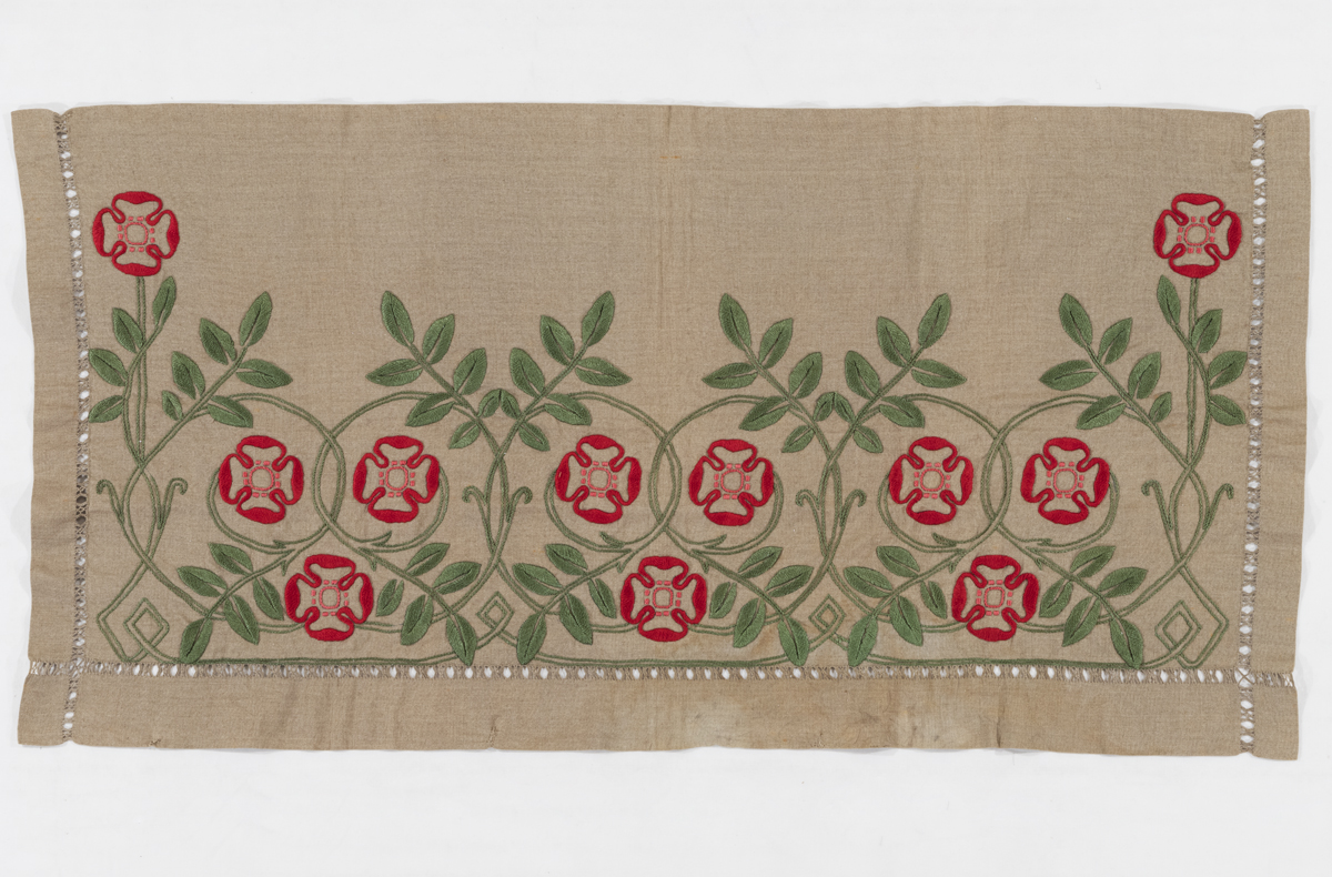 Beige textile embroidered with green and red floral pattern