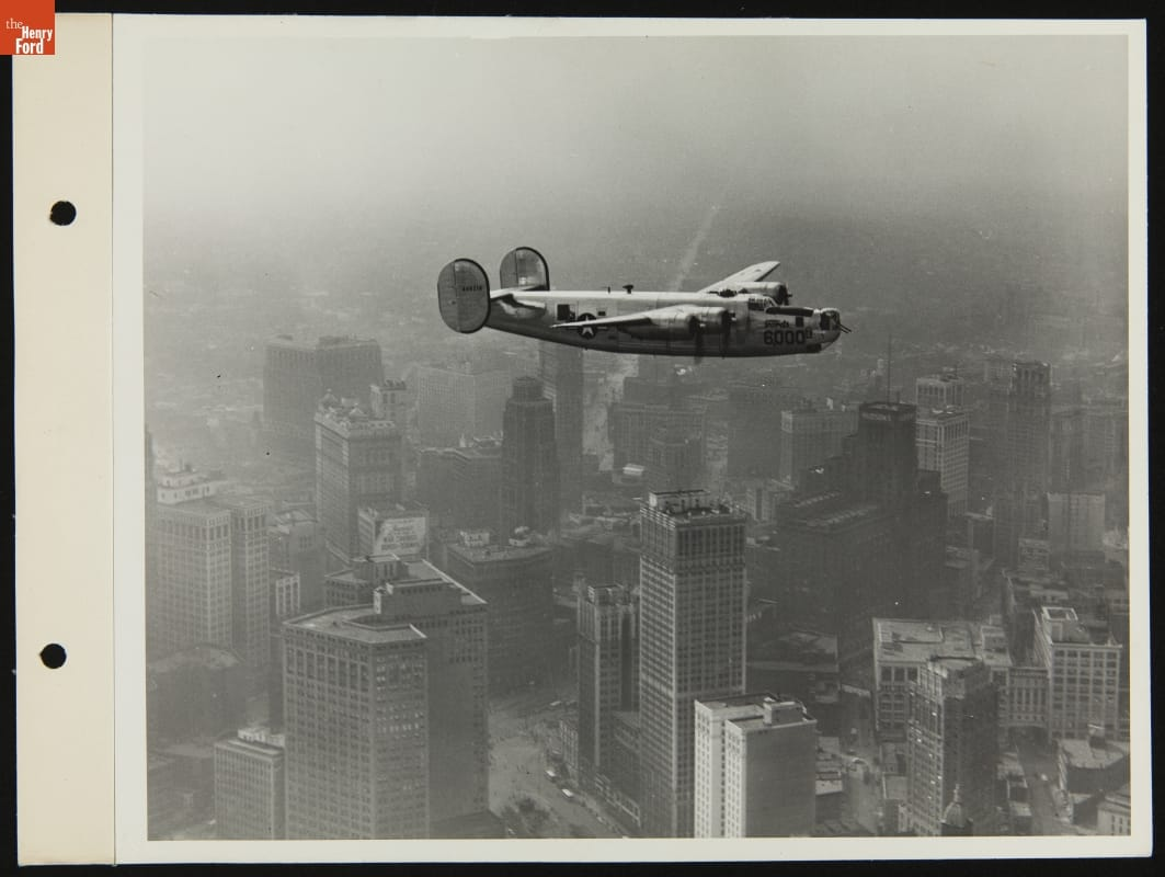 Black-and-white image of airplane flying over tall buildings.