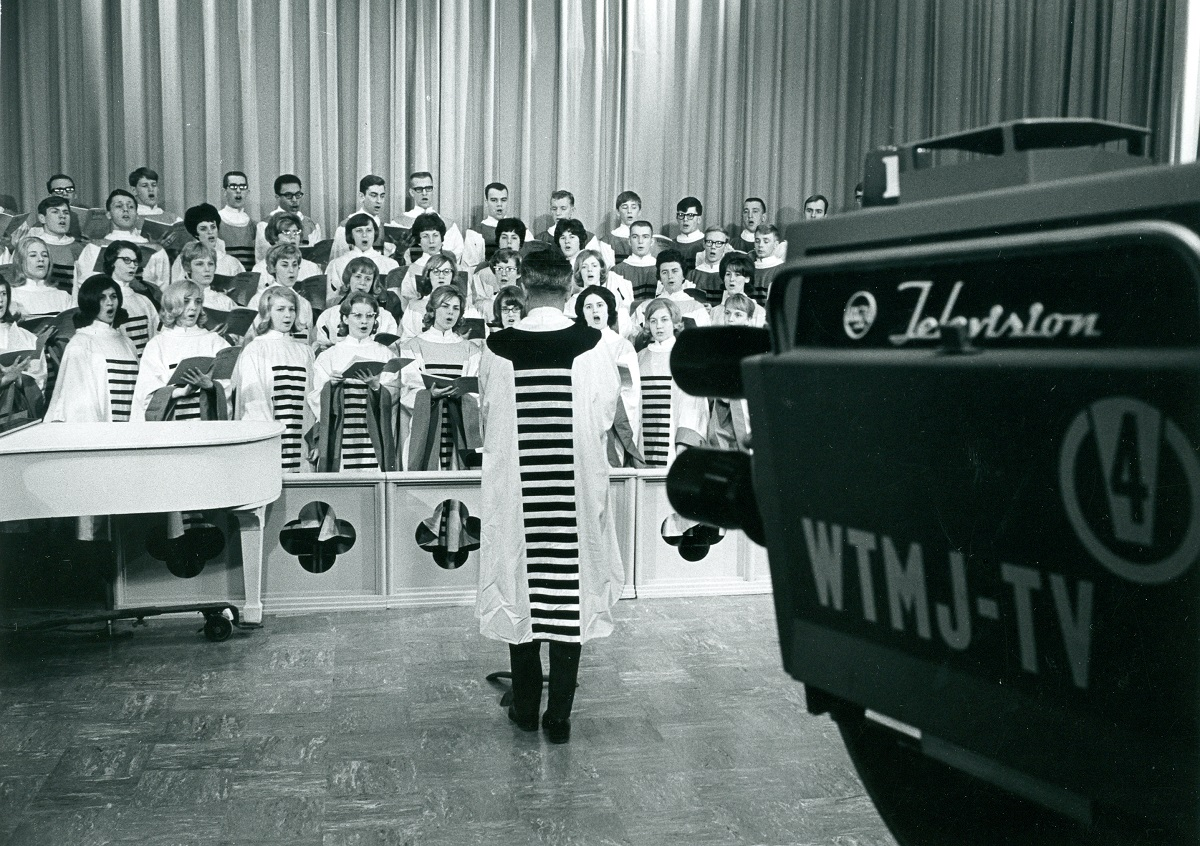 Black-and-white photo with TV camera in foreground, pointing at group of people in robes being conducted by another person in a robe