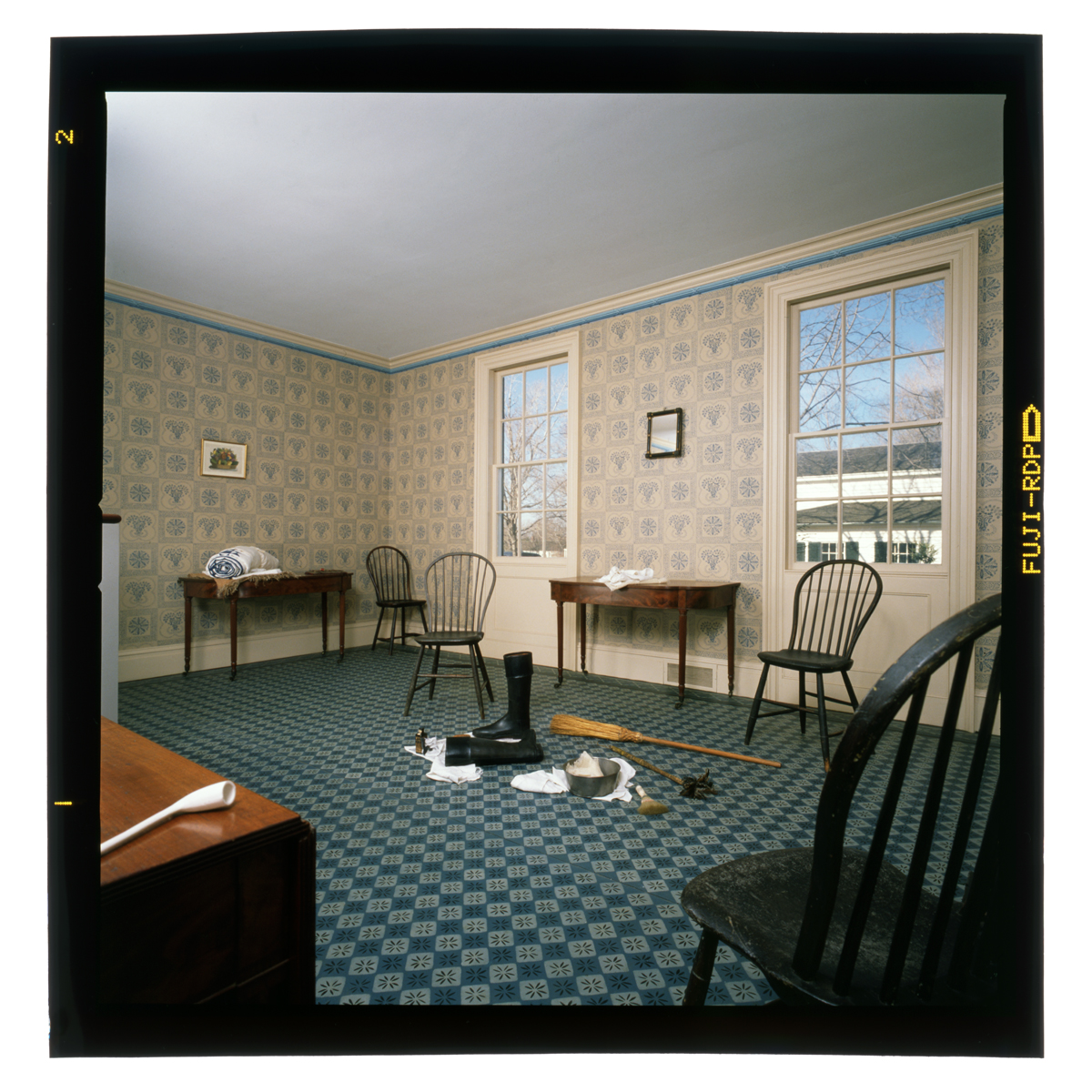 Mostly empty room with patterned floor and wallpaper, containing a few chairs and side tables