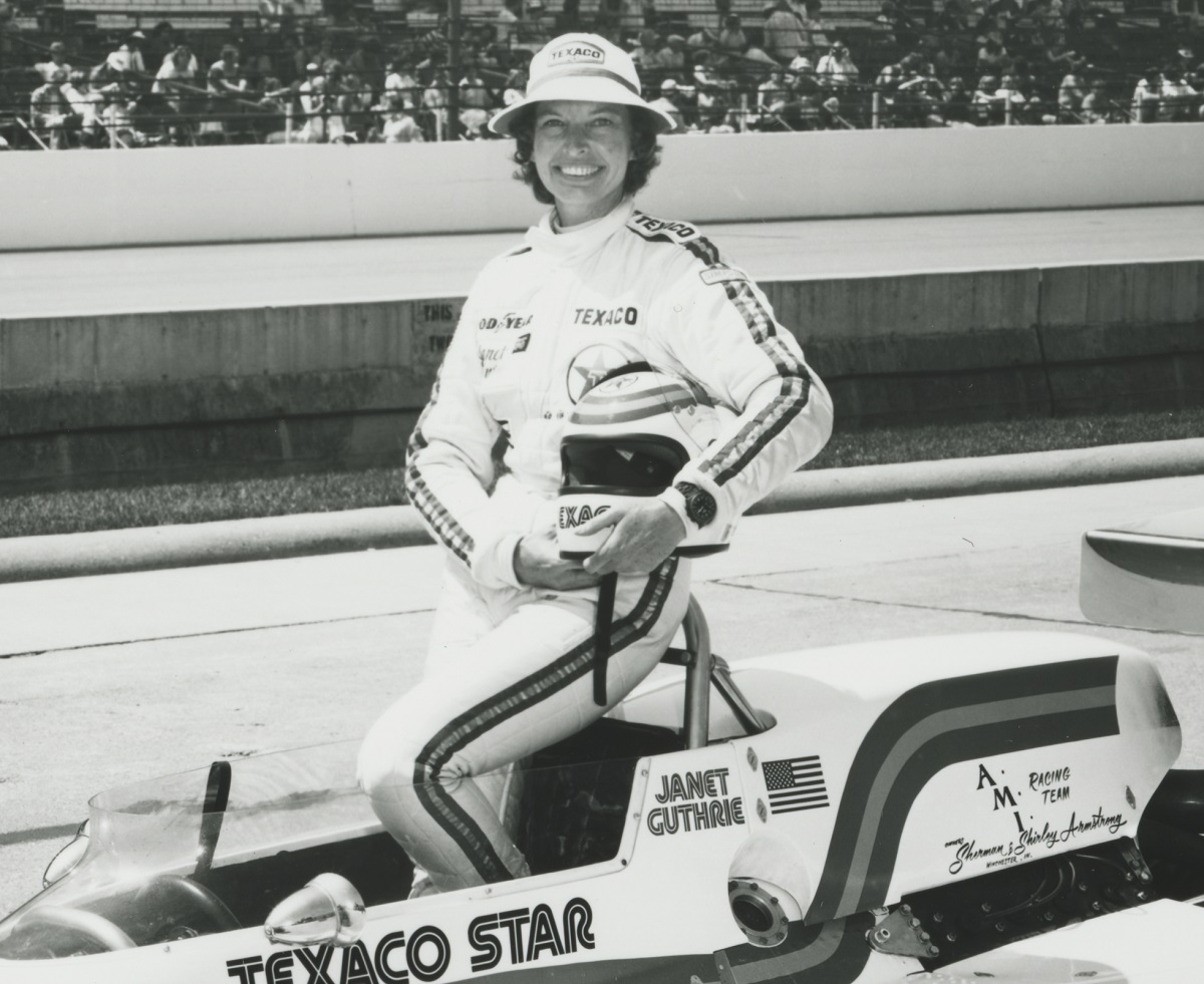 Woman in racing jumpsuit holding helmet stands in race car on track with stands of people behind her