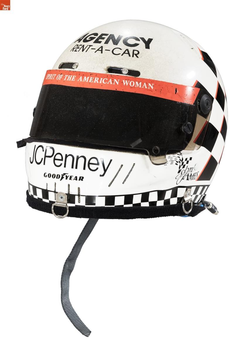 White and black helmet with dark visor and red trim; also contains text