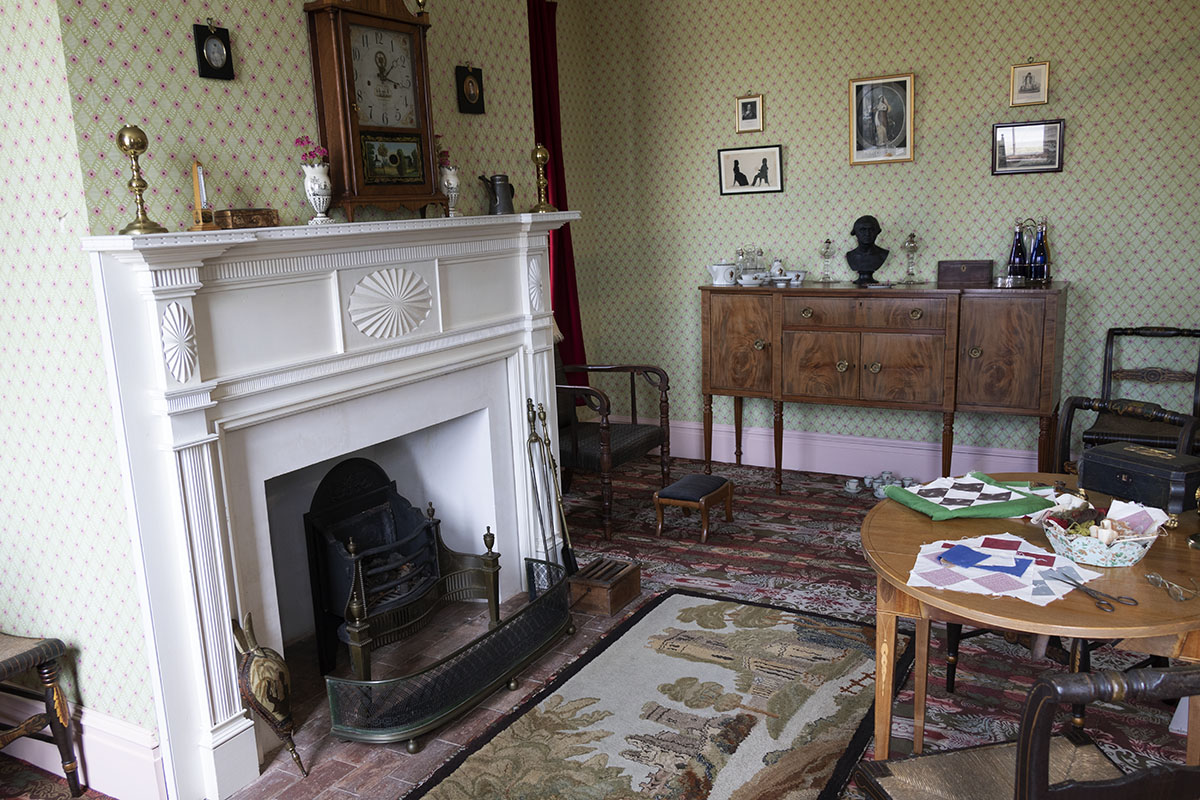 Part of carpeted and wallpapered room showing fireplace, sideboard, table and chairs