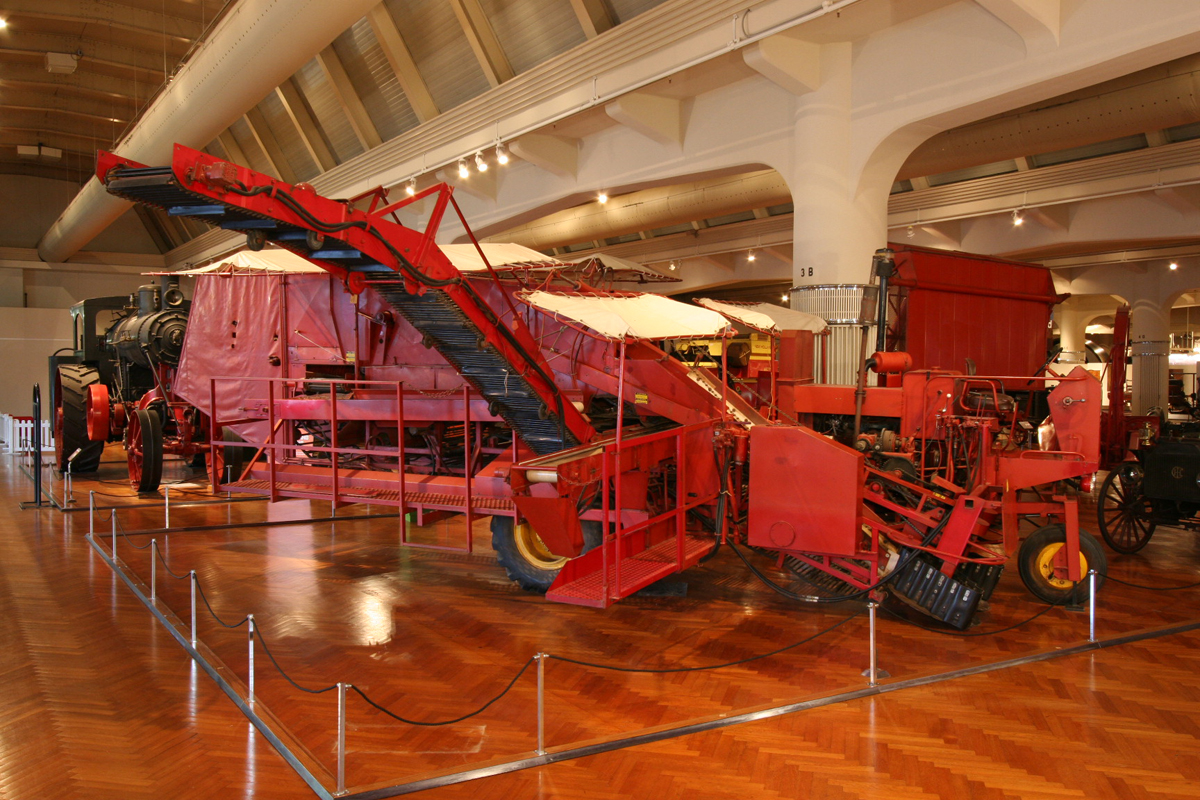 Large red farm machine in museum exhibit