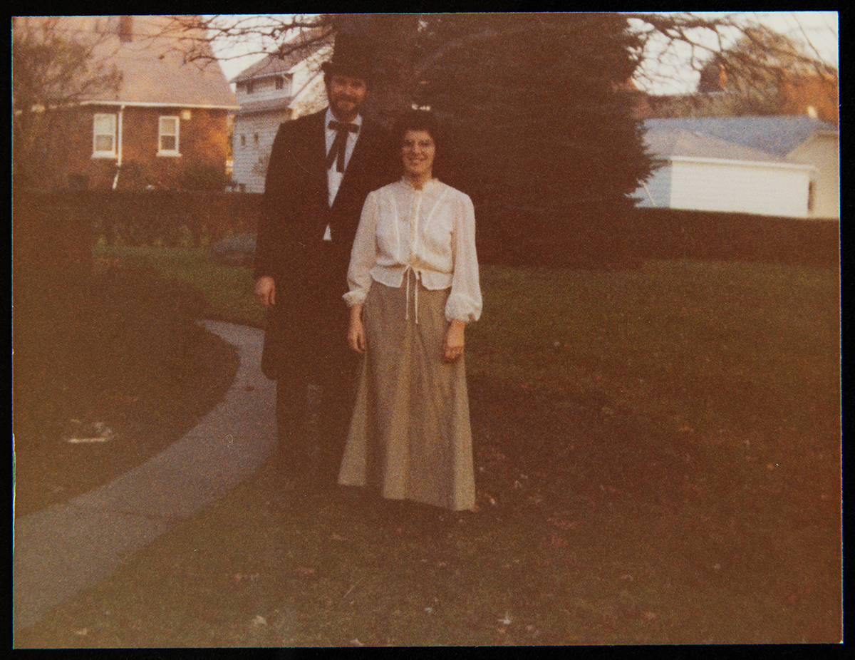 Man and woman standing outside with trees and houses behind them