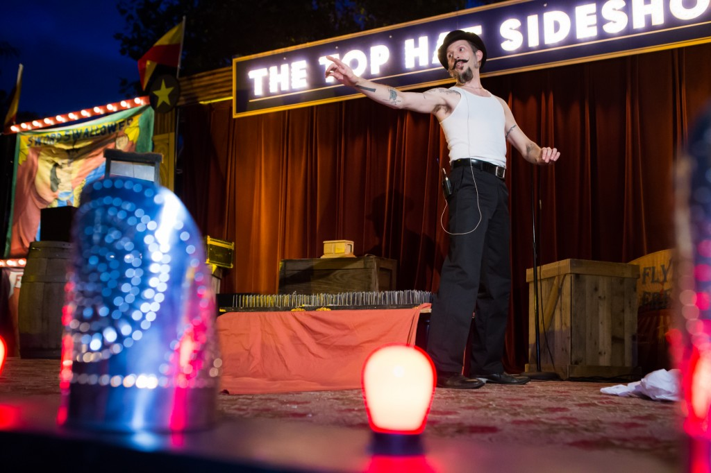 "Man in black pants and hat and white tank top points from a stage, with lighted ""Top Hat Side Show"" sign behind him"