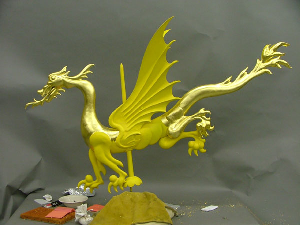 Bright gold, partially shiny and partially dull, figure of dragon with tools and implements nearby