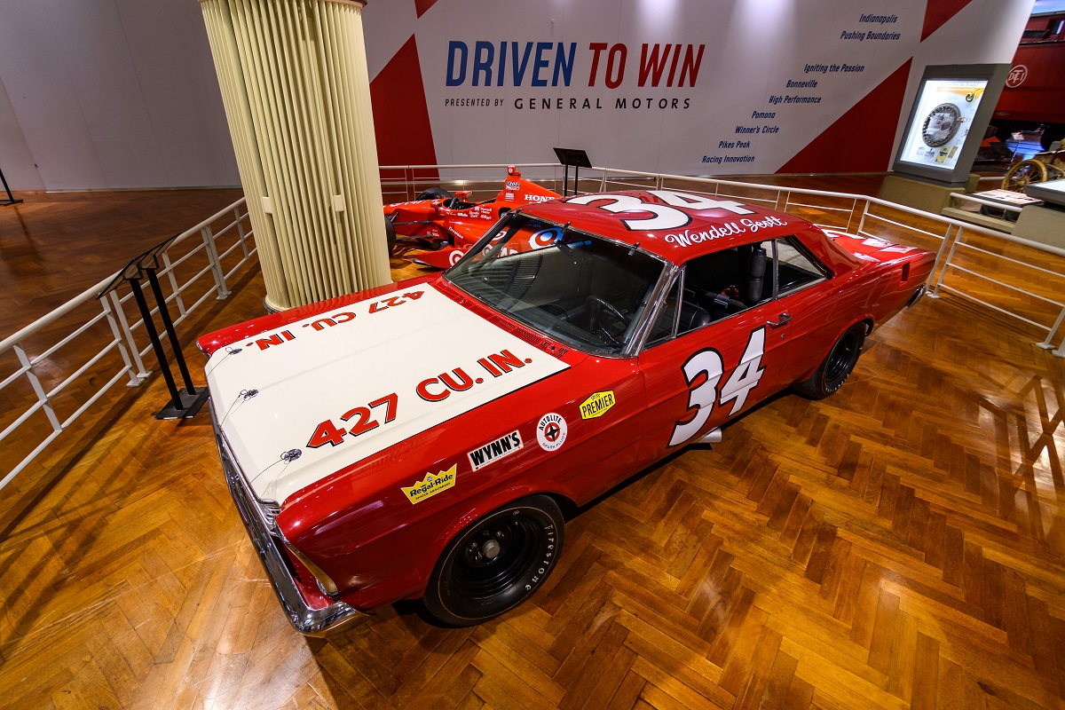 "Red car with white hood; text in multiple areas including ""34"" on door and roof, ""Wendell Scott"" on roof"