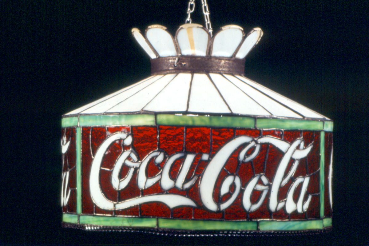 "Stained glass lamp in shades of white, green, and red, with white cursive text ""Coca-Cola"""