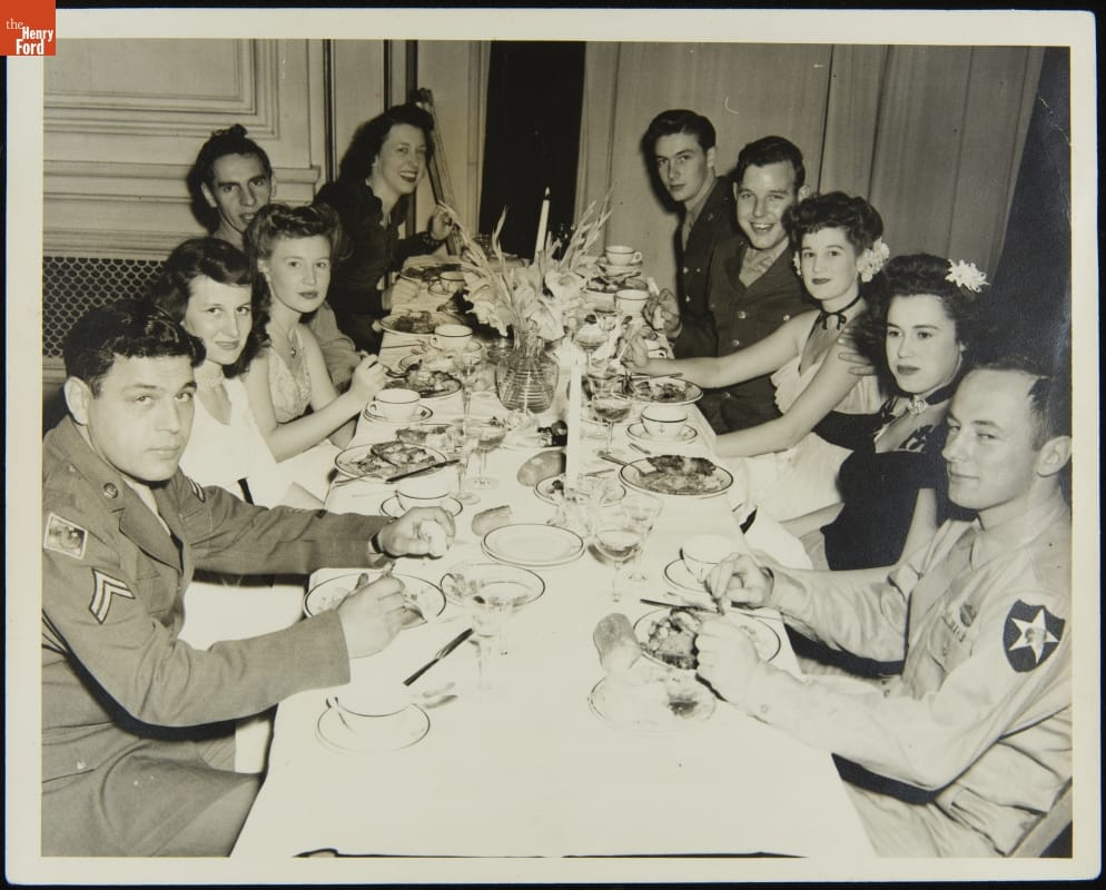 Group of men in military uniforms and women in dresses sit at a long dinner table