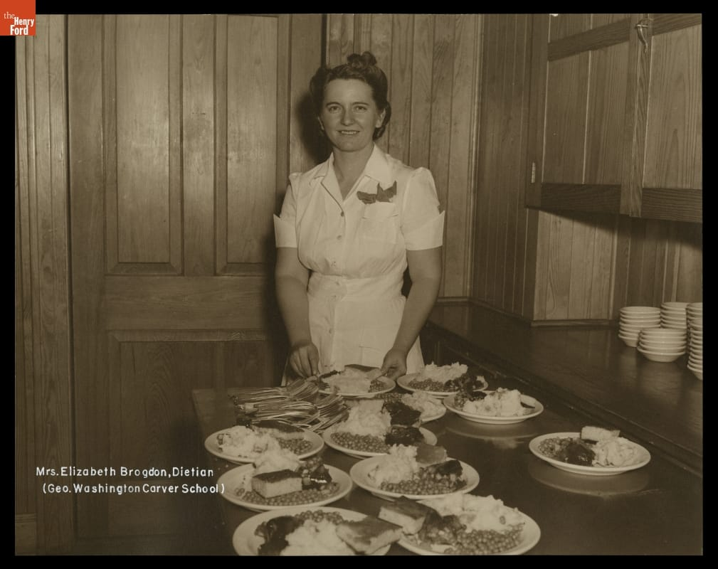 White woman stands behind table laden with plates of food in wood-paneled room