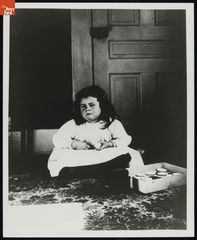Girl in white dress sitting cross-legged with somewhat grumpy expression on her face