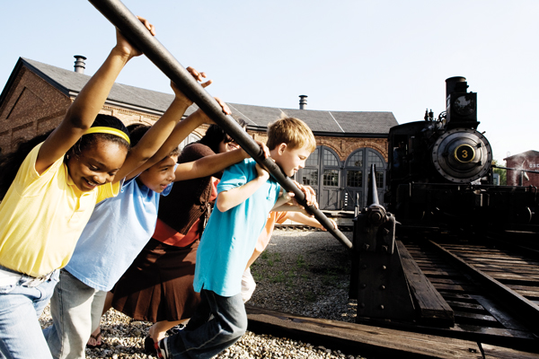 Children turning trains at Greenfield Village.