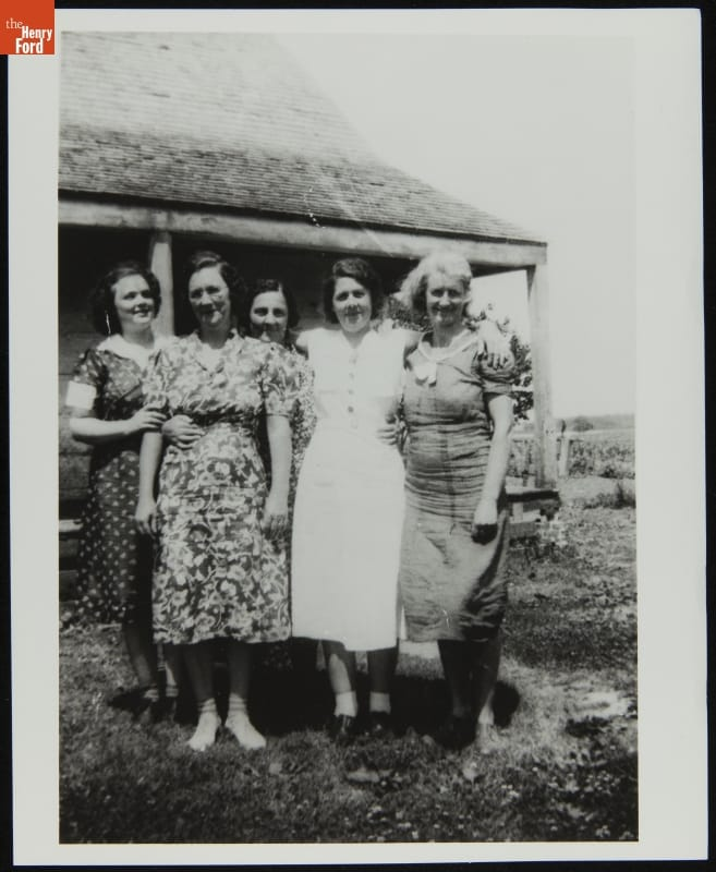 Five women posing for photo in front of a house