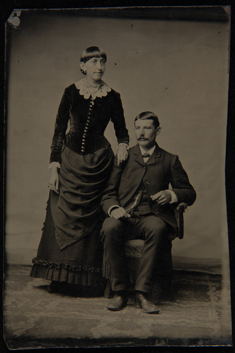 Woman with bangs wearing elaborate ensemble, standing with hand on shoulder of seated man wearing a suit