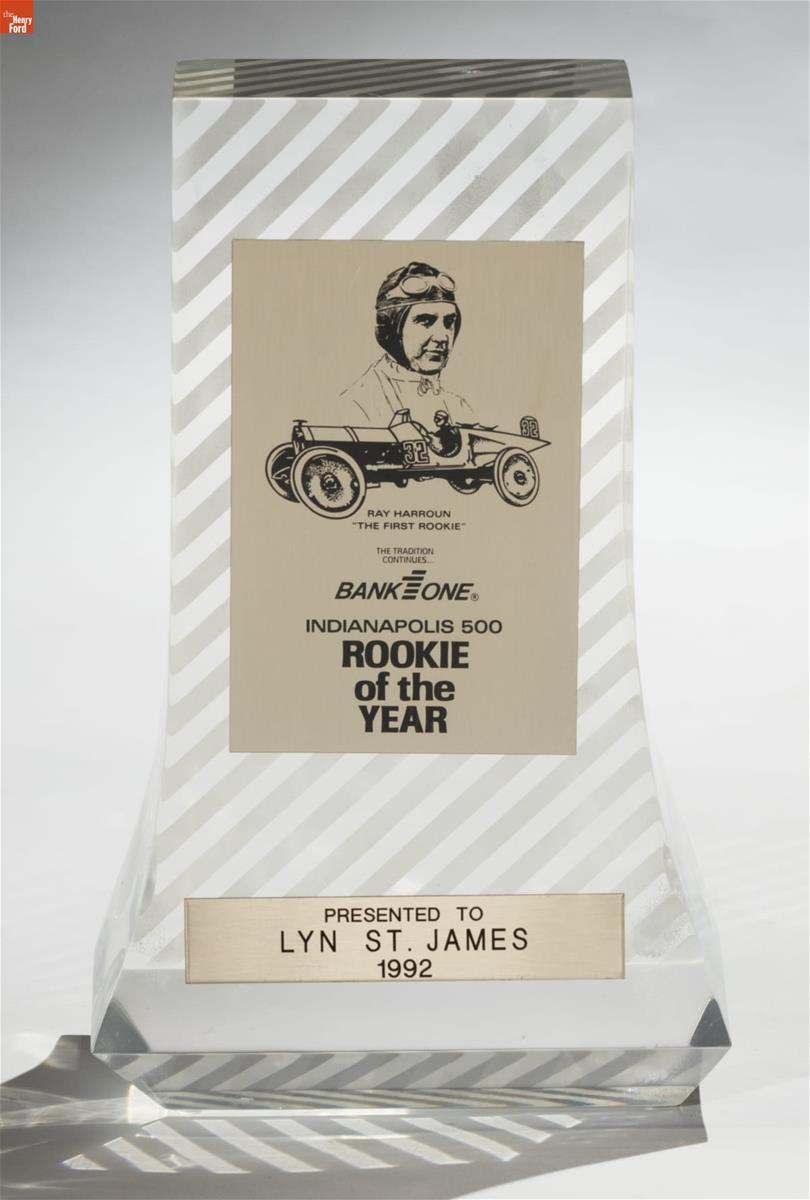 Clear glass or lucite trophy with diagonal stripes, and two panels with an image of a man in an old-fashioned racing helmet and goggles and an antique car, and text