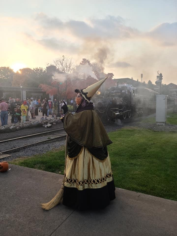 Woman in witch costume in front of a locomotive and crowd of people