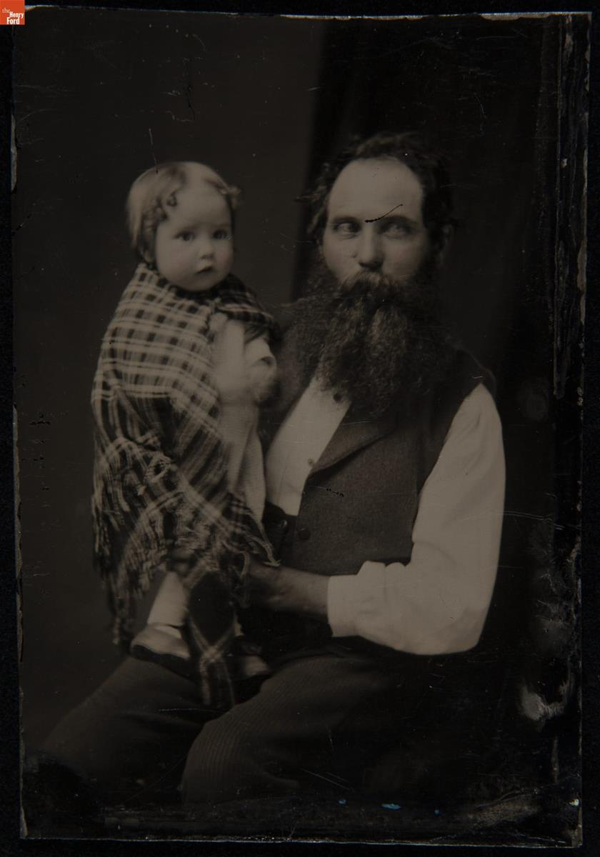 Man holding child wrapped in plaid shawl or blanket