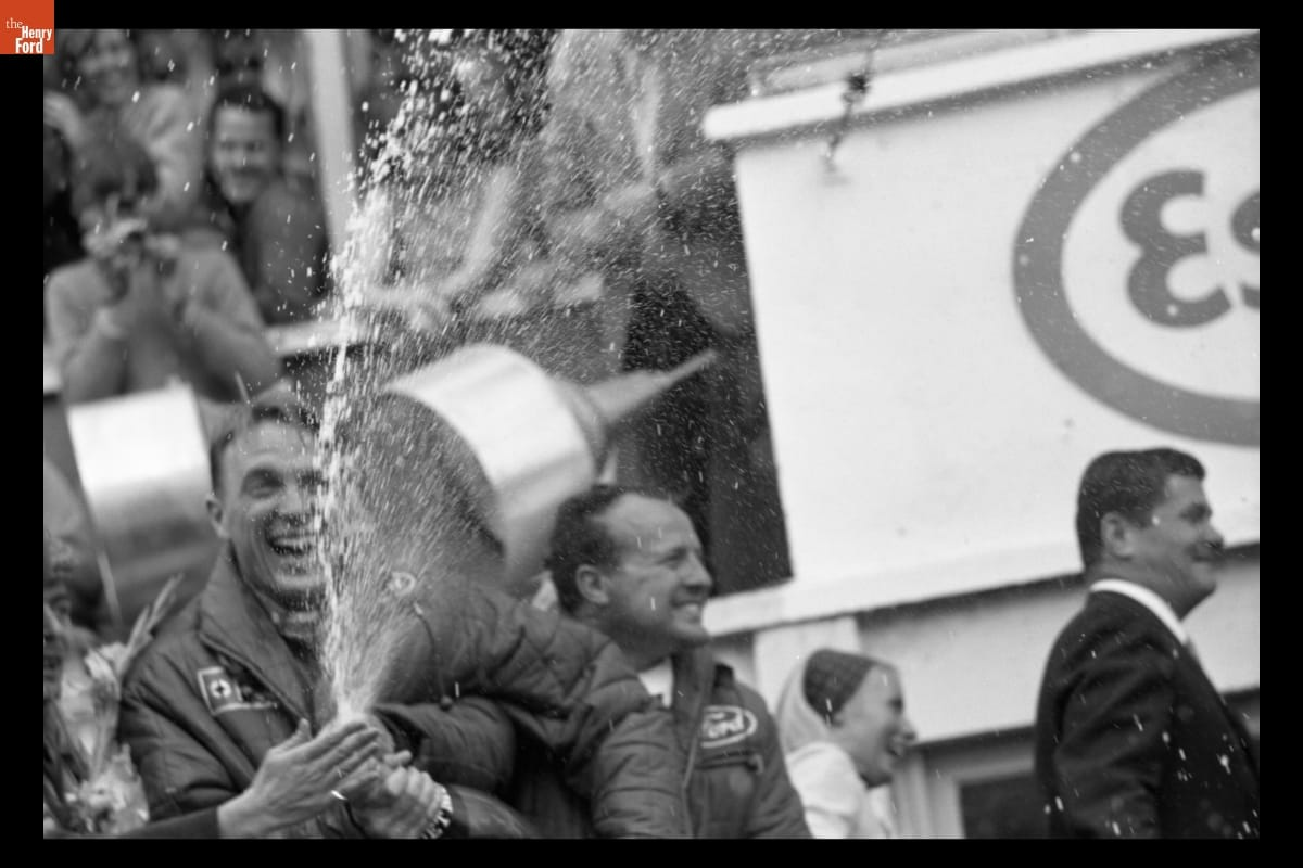 Smiling man sprays champagne from a bottle as others look on