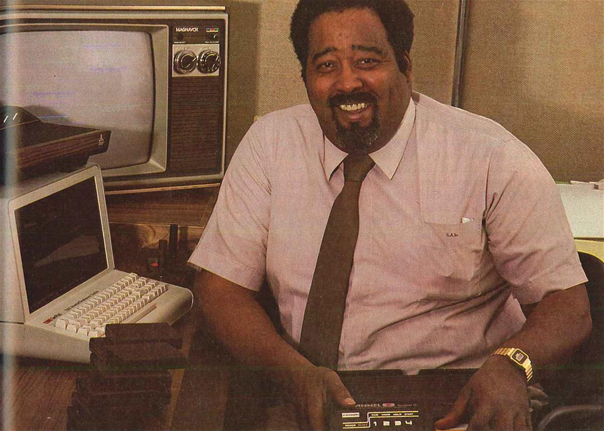 Black man with beard and mustache in shirt and tie sits by a computer and television and smiles at camera