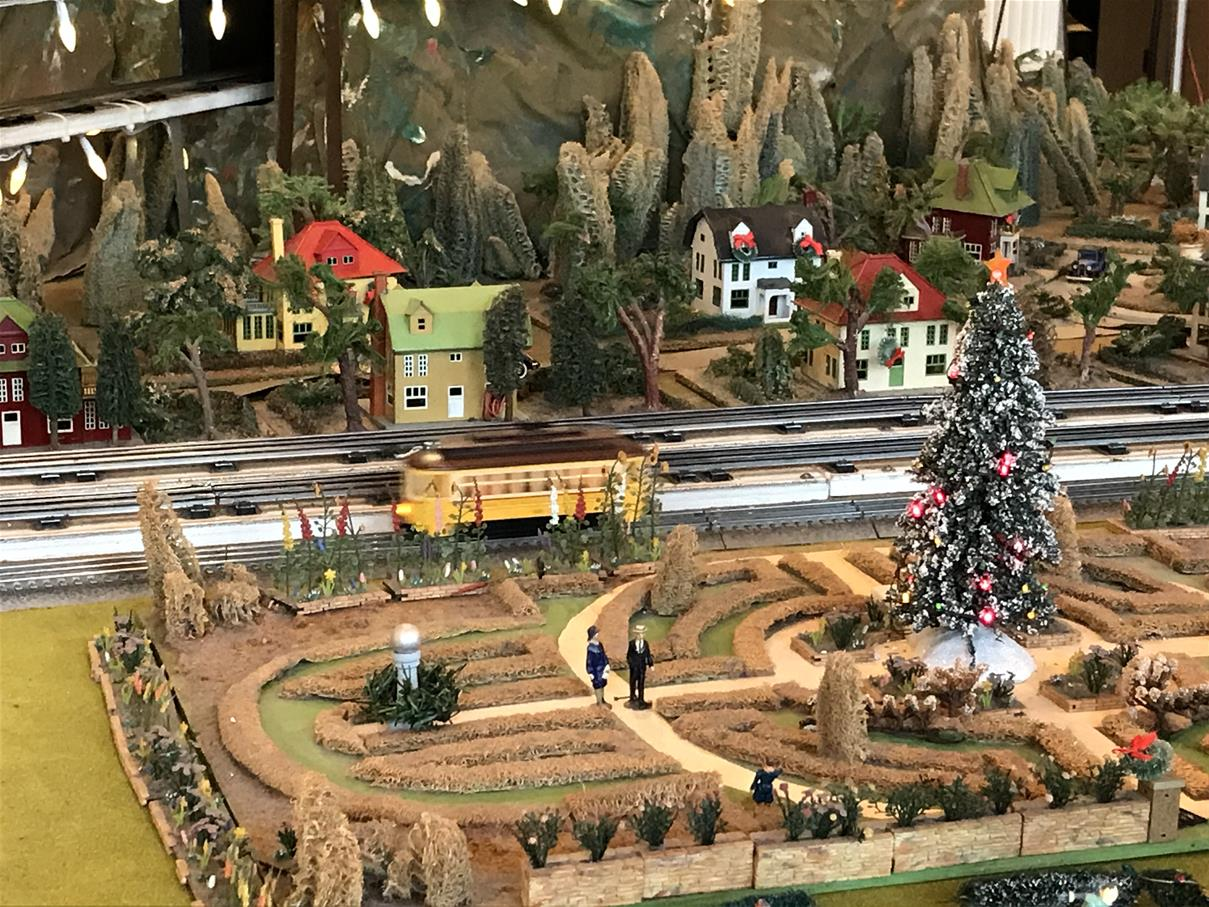 Model train layout with train tracks, train car, greenery, and houses, with Christmas decorations