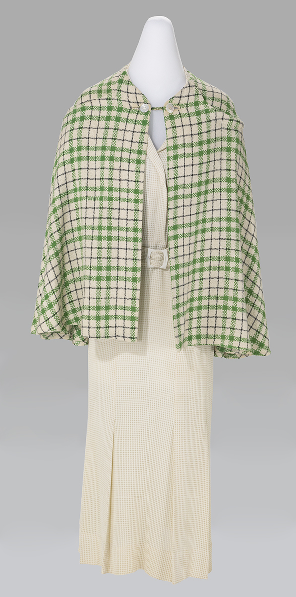 White dress with hip-length green-and-pink checked cape over it