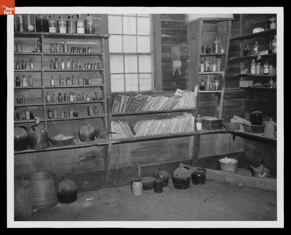 Room with one window and shelves covering almost all visible wall space, containing bottles, jars, papers, books