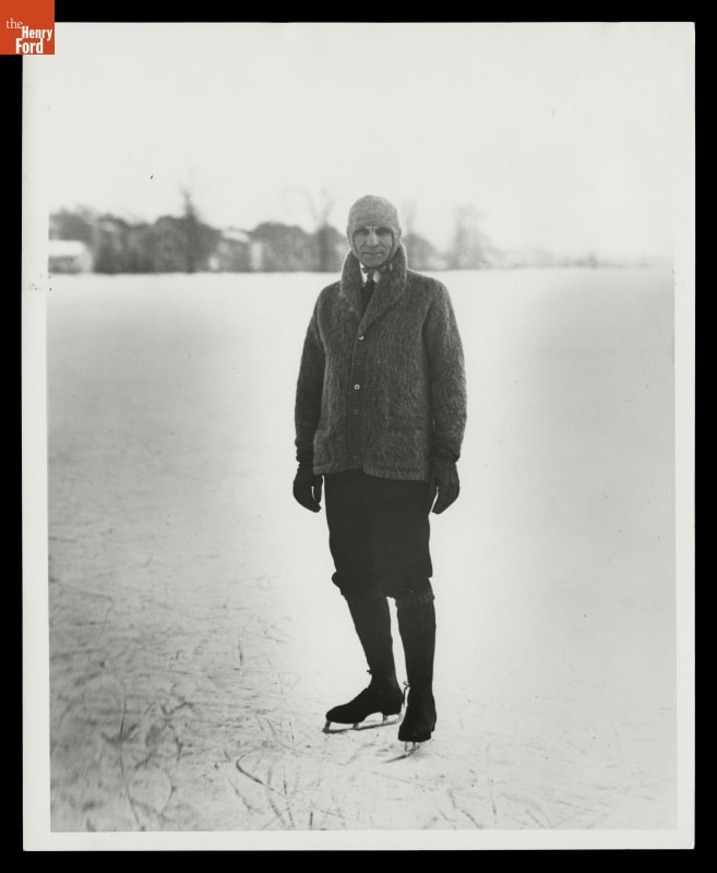 Man in cardigan with collar turned up, hat, knickers, and ice skates, on ice with trees and buildings in background