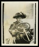 Woman in elaborate fur coat and hat behind the wheel of an open car