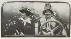 Two women in car, woman behind wheel looking at camera, woman in passenger seat looking to her right
